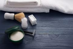 Foam, shaving brush and shaving blade on the table Stock Photos