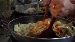 Yellow noodles are being fried in a hot frying pan in slow-motion Stock Footage