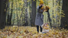 Mother and her daughter little girl walking in a autumn park - mommy and child Stock Footage