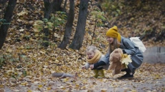 A cute little girl with blonde hair and her mom feed the red squirrels in the Stock Footage
