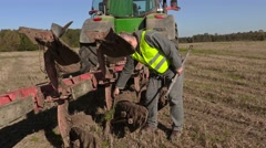 Farmer clean plow near to the tractor Stock Footage