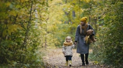 Mother and her daughter little girl walking in a autumn park - mommy, child and Stock Footage