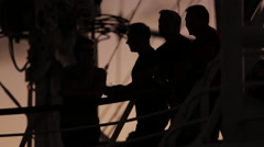 Three silhouetted tourists stand on cruise ship deck to watch sunset Stock Footage