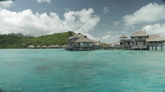Luxury large Huts over water, filmed from speed boat in Bora Bora Stock Footage