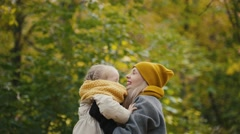 Mother and her daughter little girl playing in a autumn park - mommy throws Stock Footage
