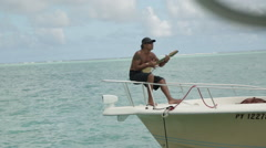 Tahitian guide plays Ukulele on his speedboat over stunning water - close up Stock Footage