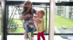Mother with her toddler daughter hanging washed laundry on stand in balcony Stock Footage