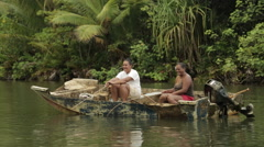 Two female Tahitian natives and dog, fish from boat, waves hello.  Stock Footage