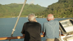 Two older men watch Taha'a Island coast slide by from cruise ship deck Stock Footage