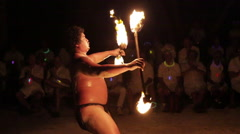 Male fire dancer juggles two spinning fire rings at once - Wide shot Stock Footage