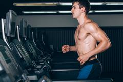 Young man in sportswear running on treadmill at gym Stock Photos