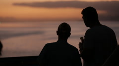 Cruise ship passengers in silhouette point to location in distance during sunset Stock Footage