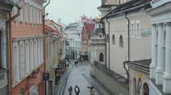 View of the old town of Vilnius, tourists walk through the narrow streets Stock Footage