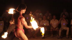 Male fire dancer juggles 2 spinning fire rings at once, throws and catches one Stock Footage