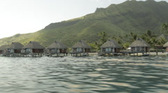 Moorea's famous huts over water filmed from fast moving speed boat Stock Footage