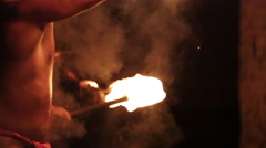 Male fire dancer slowly juggles two fire rings, throws and catches Stock Footage