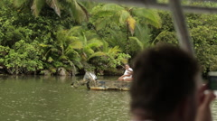 Tourists observe a passing native fishing boat with 2 native fisherwomen aboard Stock Footage