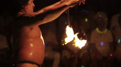 Male fire dancer juggles two spinning fire rings in sync. Close up, zooms out Stock Footage