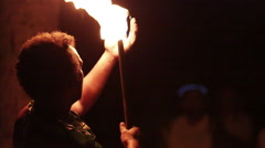 Male fire dancer uses his mouth to take flame from one end of stick to the other Stock Footage