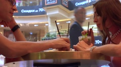 Girl and man having their cold drinks and sharing them in a shopping mall cafe Stock Footage