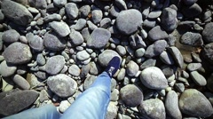 Legs are in blue jeans go on highlands on the stones next to the river Stock Footage
