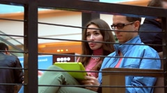 Girl and man in black rim glasses sharing tablet PC in a cafe. 4K shot Stock Footage
