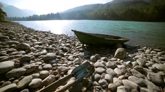 Old wooden green boat is on the shore of a mountain river, wide angle Stock Footage