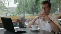 A man in a white shirt sitting in a summer cafe and thinks. It is raining Stock Footage