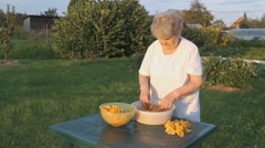 Woman 80s cleans chanterelle mushrooms in bowl Stock Footage