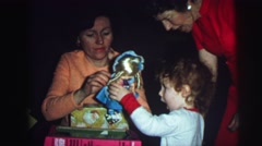 1974: christmas tree is seen with child opening presents LYNBROOK, NEW YORK Stock Footage