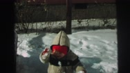 1974: well bundled boy outdoor playing in the snow LYNBROOK, NEW YORK Stock Footage