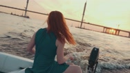 Red hair girl in turquoise dress on motor boat. Beautiful sunset. Wave hand Stock Footage
