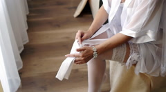 Bride pulling up stockings getting ready for her wedding in her bedroom - side Stock Footage