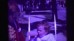 1974: redhead big brother pushing around kid sister in stroller on sidewalk Stock Footage