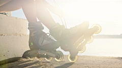 Woman is going rollerblading. Sitting on a bench in a park Stock Footage