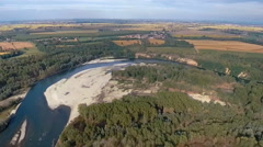 Aerial shot of a sandy river meander surrounded by a forest and fields Stock Footage
