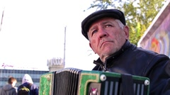 Grandpa sits in the city and plays the accordion Stock Footage