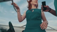 Young girl in turquoise dress in motor boat talk with man hold smartphone. Wind Stock Footage