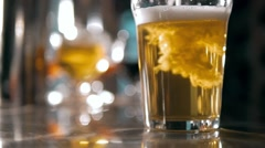 Beer into glass with a lot of bubles and foam super close up slow motion Stock Footage