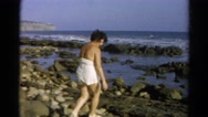 1966: woman exploring sea shore searches for shells in the salty ocean water Stock Footage
