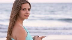 Young woman stays at sea beach holding and lookin at smartphone Stock Footage