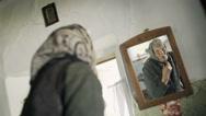 Elderly lady adjusting her kerchief in a mirror Stock Footage