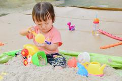 Baby playing toys in sand at home, Sand play is fantastic in aiding a toddler s Stock Photos