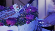 Woman take piece of huge cake with roses by knife at celebration event Stock Footage
