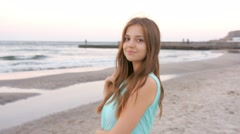 Beautiful girl stays at the beach near sea Stock Footage