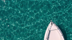 Aerial - Top view of motor boat anchored in clear water with a bow visible only Stock Footage
