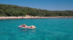 Young woman lying and relaxing on swimming pool floatie in crystal clear ocean Stock Footage