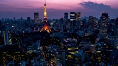 Evening Tokyo city view with Tokyo Tower lighting up. 4K time lapse zoom out. Stock Footage