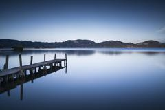 Wooden pier or jetty on blue lake sunset and sky reflection water. Long expos Stock Photos