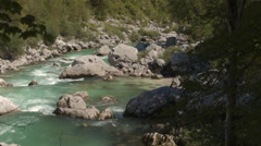 AERIAL, CLOSE UP: Beautiful emerald maintain river running between sharp rocks Stock Footage